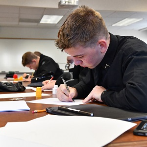 Cadet writing during an educational event