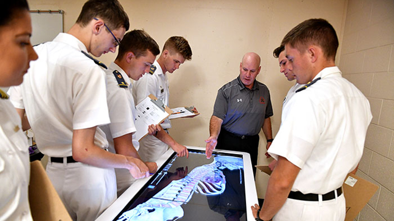 Col. Mike Krackow, professor of physical education, shows cadets various uses of the Anatomage table.