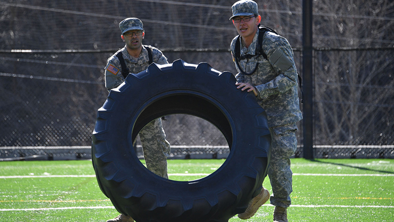 Cadets working together to flip a tire during Breakout.