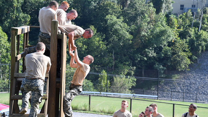 Cadets aiding each other in scaling a wall during Crucible.