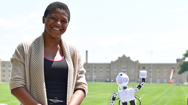 Miyah Boyd '20 pauses with her robot, JD, on the porch of Moody Hall.