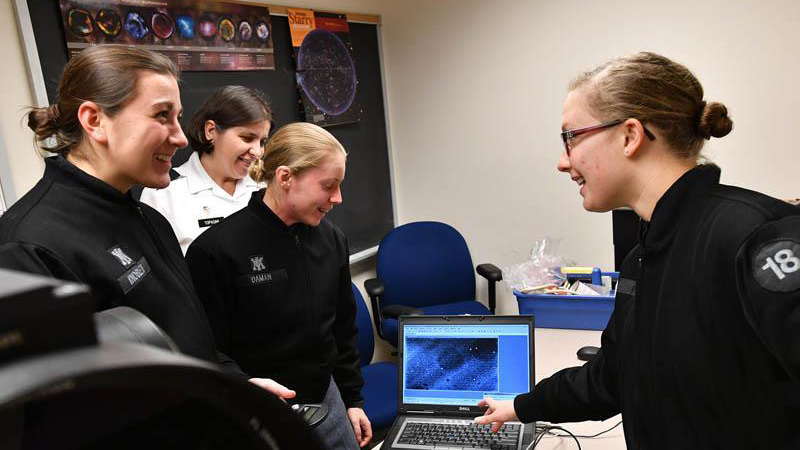 Julianne Knoblett '20, Eryn Daman '18, and Marlene Haag '18, each members of WiSE, look at an image taken by a telescope with Col. Daniela Topasna, professor of physics and astronomy.